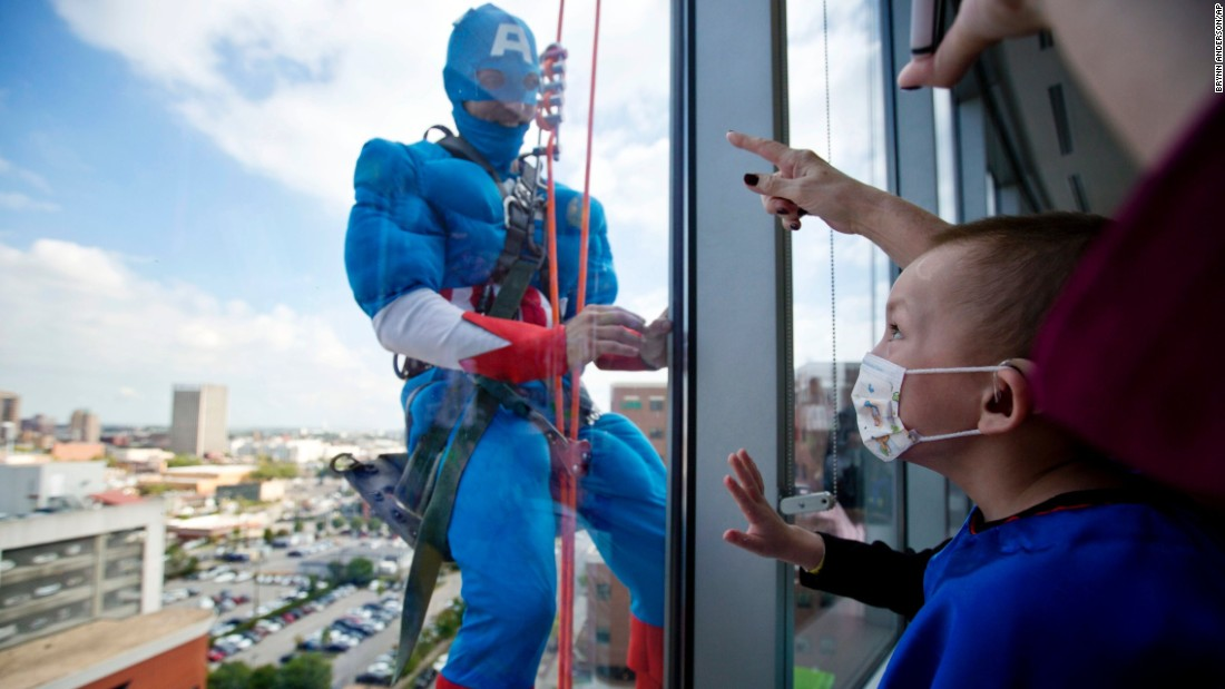 Landon Fox, 5, looks up to see a window-washer dressed as his favorite superhero, Captain America, at Benjamin Russell Hospital for Children on Wednesday, October 7, in Birmingham, Alabama.