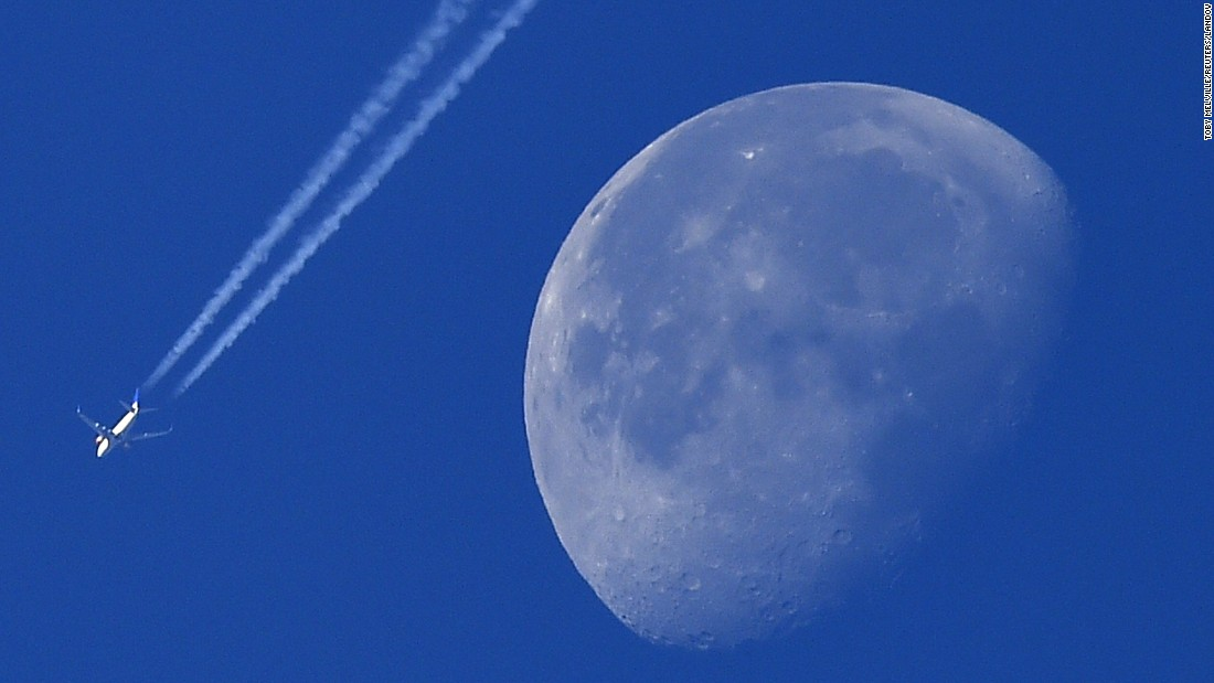 A passenger plane is seen with the moon over west London on Friday, October 2.