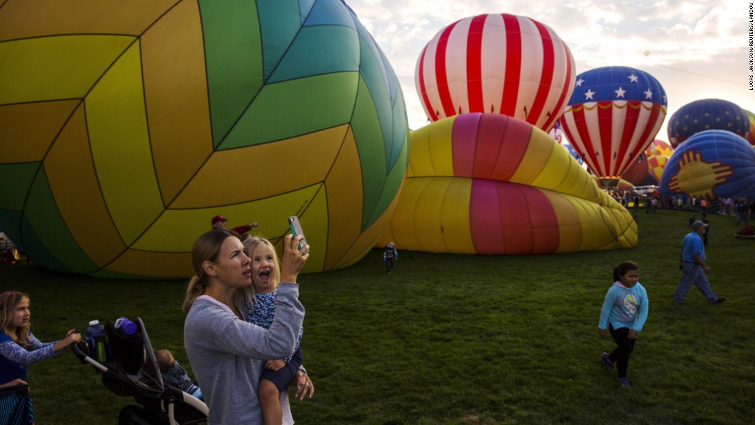 Attendees watch and take pictures as hundreds of hot air balloons lift off on the first day of the 2015 Albuquerque International Balloon Fiesta in New Mexico on Saturday, October 3.