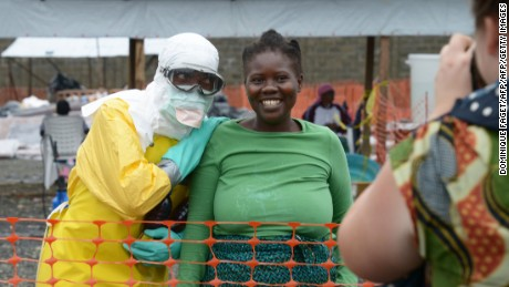 A health worker, wearing Personal Protective Equipment (PPE), and a woman pose on September 7, 2014 inside the high-risk area at Elwa hospital in Monrovia, which is run by the non-governmental  international organization Medecins Sans Frontieres (Doctors without Borders -- MSF). US President Barack Obama said in an interview aired on September 7 the US military would help in the fight against fast-spreading Ebola in Africa, but warned it would be months before the epidemic slowed. The tropical virus, transmitted through contact with infected bodily fluids, has killed 2,100 people in four countries since the start of the year -- more than half of them in Liberia.   AFP PHOTO / DOMINIQUE FAGET        (Photo credit should read DOMINIQUE FAGET/AFP/Getty Images)