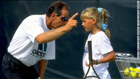 Coach Nick Bollettieri gives instructions to a young Anna Kournikova during training at his academy.