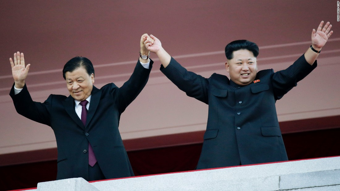 North Korean leader Kim Jong Un, right, stands with visiting Chinese official Liu Yunshan above the parade in Pyongyang.