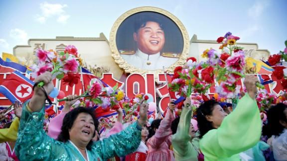 North Koreans parade beneath a portrait of leader Kim Jong Un.
