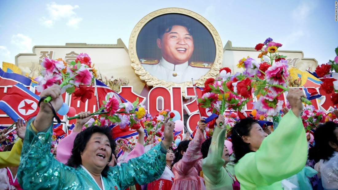 North Koreans parade beneath a portrait of leader Kim Jong Un.