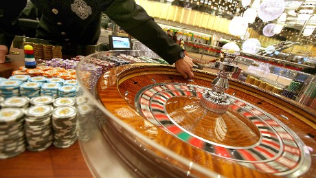 A roulette dealer waits at one of the new tables at the Grand Lisboa hotel and casino during a press preview ahead of the casino's opening in Macau, 11 February 2007.  Billionaire tycoon Stanley Ho, who for 40 years held a monopoly on gambling in the southern Chinese territory and has seen his market share of the business slide with the opening since 2004 of rival Las Vegas-style casinos, launched his comeback campaign in Macau by opening a huge casino 11 February he hopes will bring punters back to his once-dominant gaming halls.     AFP PHOTO/Samantha SIN        (Photo credit should read SAMANTHA SIN/AFP/Getty Images)