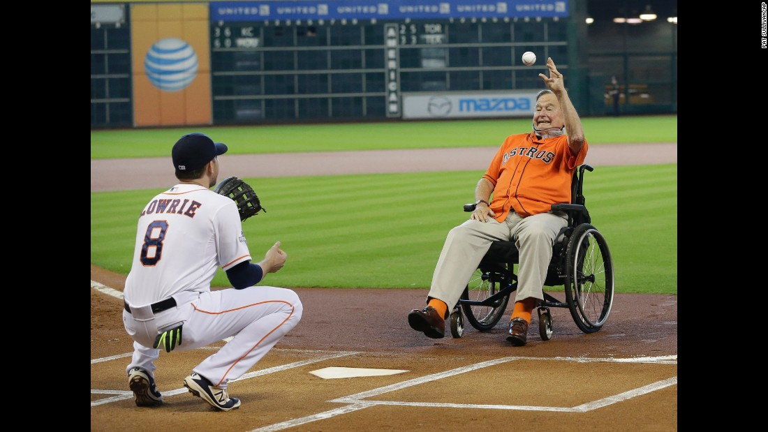 Former U.S. President George H.W. Bush throws out the ceremonial first pitch to Houston's Jed Lowrie before Game 3 of the American League Division Series on Sunday, October 11.