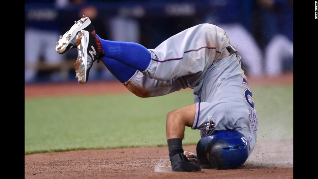 Rougned Odor, second baseman for the Texas Rangers, lands after flipping at home plate to avoid a tag Friday, October 9, in Toronto. Odor scored on a sacrifice fly for the Rangers, who took a 2-0 lead over Toronto in the American League Division Series.