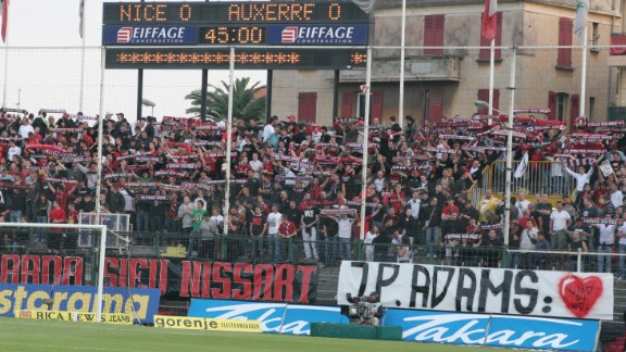 """Nice fans display a banner reading """"J-P Adams: One of Us"""" on 28 April 2007, ahead of their former player's sons -- Laurent and Frédéric -- symbolically kicking off a match against Auxerre in tribute to their father."""