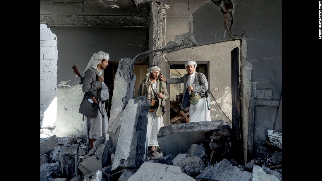 Three fighters stand in the rubble of a sheik's home in September.