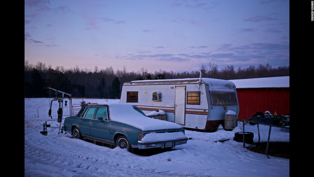A car and an abandoned trailer sit on Faron Cox's property at sunrise.