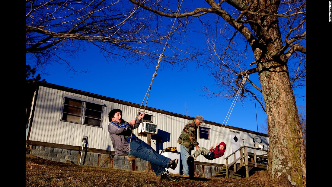 "Faron Cox Jr., 7, and Skylor Cox, 3, play on rope swings outside of their home. ""When I first had my first three kids, back in the 70s, I thought that was it,"" Faron Cox Sr. said. ""I wasn't thinking about having another wife or more kids and then more kids. It never entered my mind."""