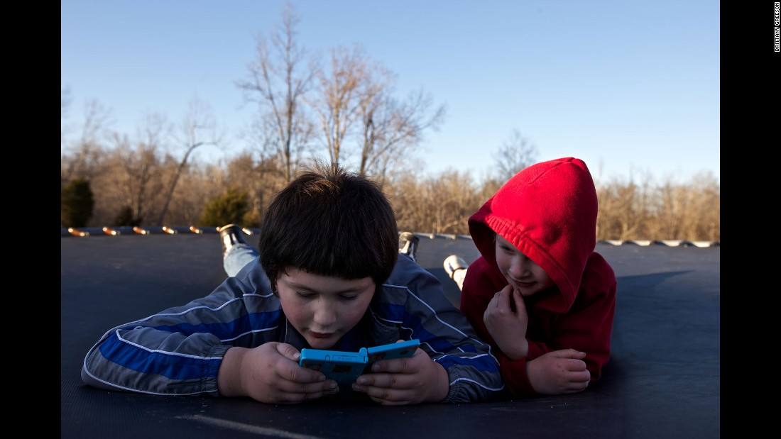 Skylor and Faron Jr. play a video game while resting on a trampoline at their home.