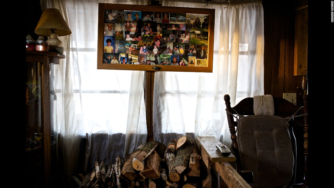 A frame with an array of family photos hangs over a freshly cut stack of firewood at the family's home.