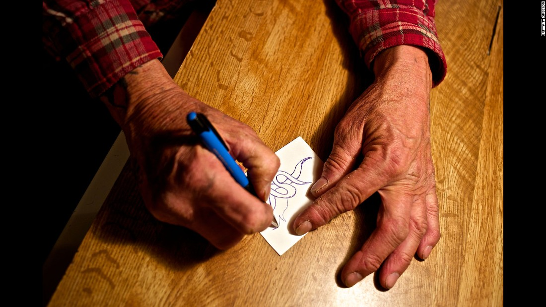 Faron Sr. doodles on a small piece of paper at his home. He said he loves to draw different shapes and patterns as a form of stress relief.