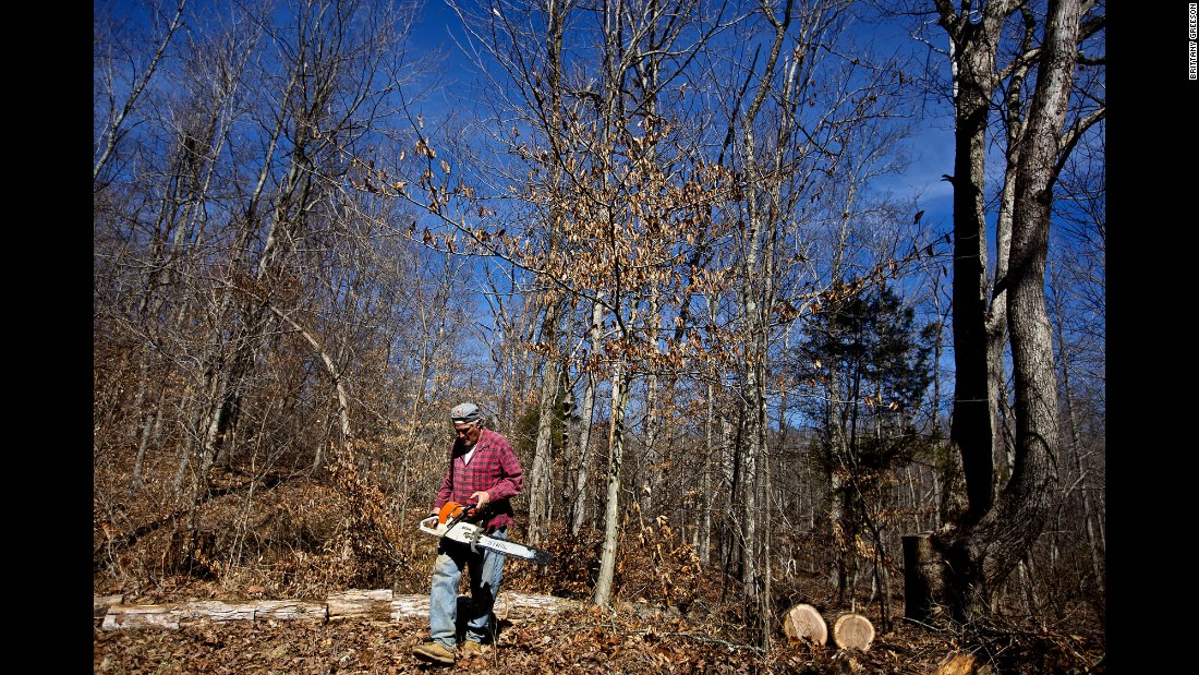 Faron Sr. spends his morning cutting down trees to be later used as firewood.