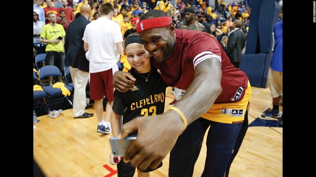 Basketball star LeBron James takes a photo with a young fan after an NBA preseason game in Cincinnati on Wednesday, October 7.