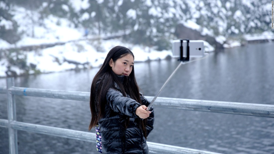 A woman uses a selfie stick at Luoji Mountain after a heavy snow in Puge County, China, on Monday, October 12.