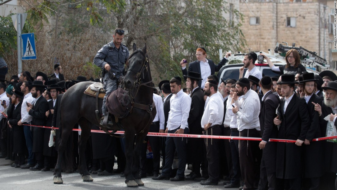 A member of Israel's security forces cordons off the site in Jerusalem where a Palestinian man drove into a bus stop and carried out a stabbing attack on October 13.