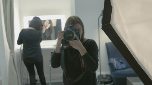 Photographer Julia Holland sets her shot as Beckingham prepares to pose topless following breast reconstruction surgery.