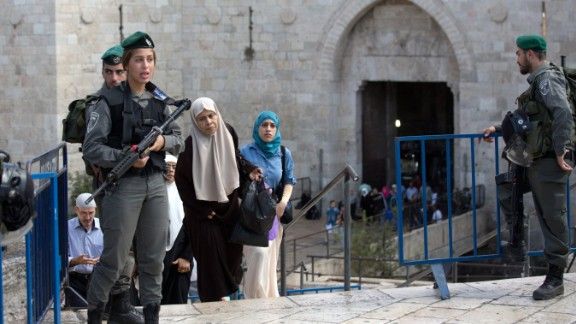 Palestinian women walk past Israeli border police at the Damascus Gate at the entrance of the Old City in East Jerusalem in 2015.