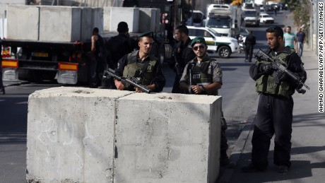 Israeli security forces gather at the site where a road block is being set up.