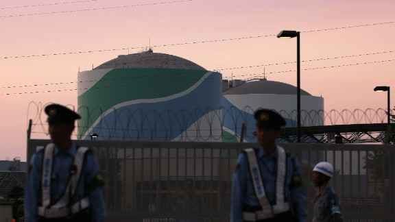 Nuclear reactor buildings of the Kyushu Electric Power Sendai nuclear power plant are seen behind police officers standing guard in the twilight in Satsumasendai in Kagoshima prefecture, on Japan