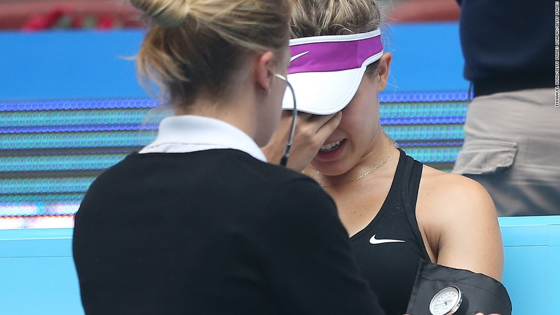 A visibly distressed Bouchard is pictured receiving treatment on court at the China Open before her retirement.