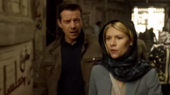 """Claire Danes star of hit U.S. TV series """"Homeland"""" walks past graffiti on a wall that says in Arabic: """"Homeland is NOT a series."""""""