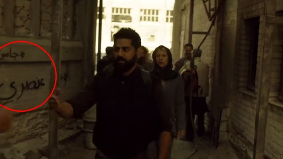 """Danes as Carrie Mathison walking through a fictional Syrian refugee camp past the graffiti slogan: """"Homeland is racist."""""""