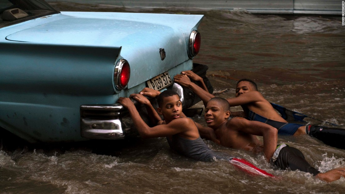 Children hang from the bumper of a vintage car as they play in a flooded street in Havana, Cuba, on Wednesday, October 14. The street was flooded after heavy rain.