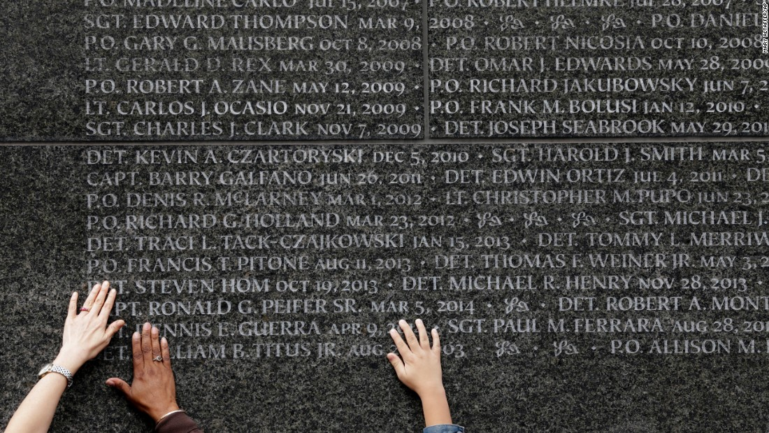 Family members of police officers who died in the line of duty touch the names of their loved ones during a ceremony at the Police Memorial Wall in New York on Tuesday, October 13.