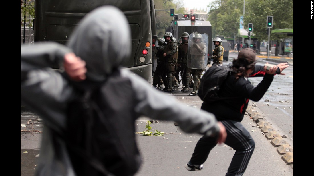 Protesters throw stones at police during a march in Santiago, Chile, on Monday, October 12. The march was organized by indigenous groups demanding autonomy and the recovery of ancestral land. Protesters also demonstrated against Chile's anti-terrorism law.