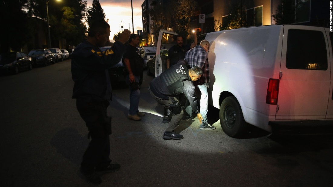 A man in Los Angeles is detained by Immigration and Customs Enforcement agents on Wednesday, October 14. Agents said the undocumented immigrant was a convicted criminal and gang member who had previously been deported and would be again.