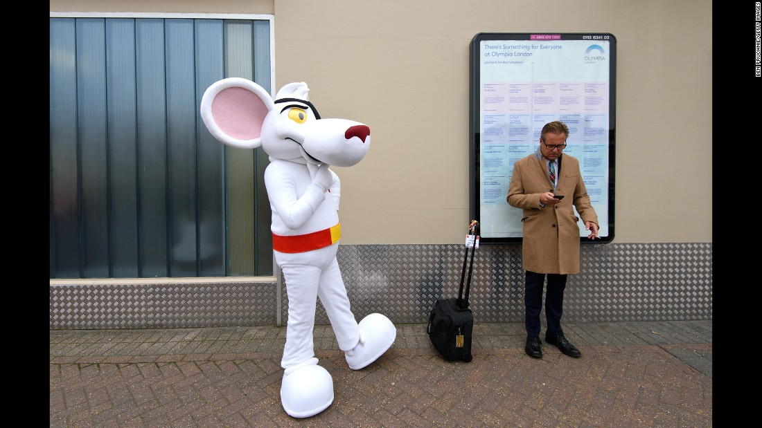 A performer dressed as British cartoon character Danger Mouse waits outside an exhibition center in London on Tuesday, October 13.