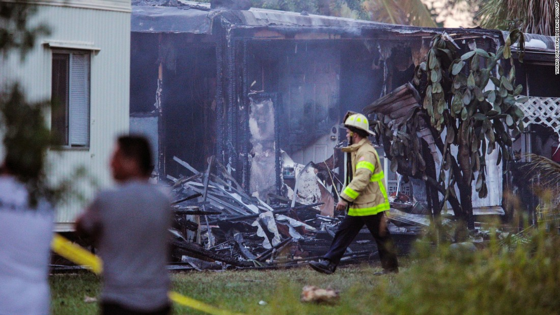 "A firefighter walks by a charred mobile home that was destroyed after <a href=""http://www.cnn.com/2015/10/14/us/lake-worth-florida-plane-crash/"" target=""_blank"">a small plane crashed</a> in Lake Worth, Florida, on Tuesday, October 13. The pilot of the plane was killed, as was one person on the ground, according to the National Transportation Safety Board."