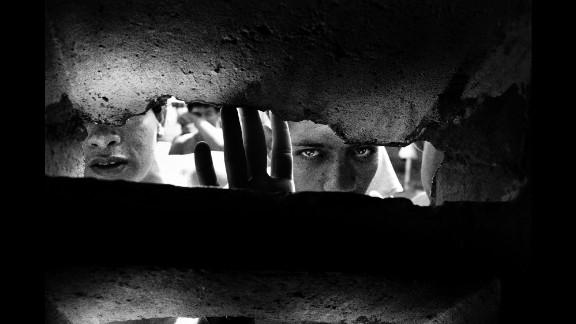Prisoners peer out of an opening in Caracas, Venezuela, in 2009.