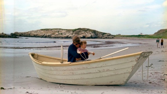 Kennedy and his son, John Jr., in a rowboat in Newport, Rhode Island. Benjamin C. Bradlee, editor of the Washington Post, and Antoinette Bradlee walk in the background.