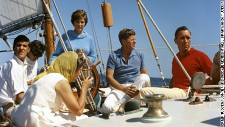 "President Kennedy vacations at Hammersmith Farm. L-R: Mrs. Hugh D. Auchincloss, John Forbes Kerry, [unidentified], Janet Auchincloss (at wheel), President Kennedy, [unidentified]. Aboard the USCG yacht ""Manitou"" in Narragansett Bay, Rhode Island."
