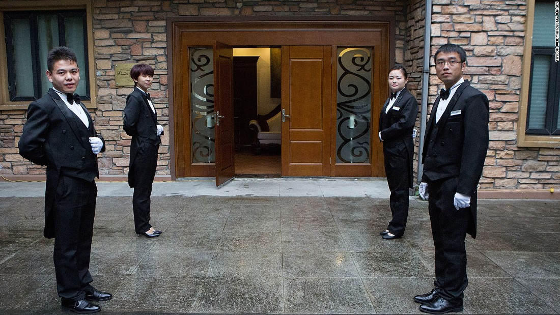 Students wait outside to greet guests for a formal dinner at The International Butler Academy China on September 16, 2014 in Chengdu, China.