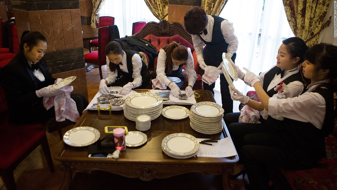 Butlery students polish china and silverware in preparation for a formal dinner on September 16, 2014 in Chengdu, China.