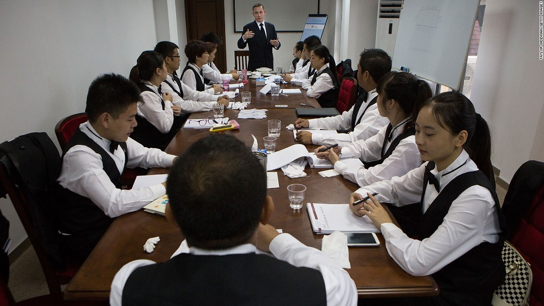 Christopher Noble, an instructor at The International Butler Academy China, teaches a class on serving a formal dinner on September 16, 2014.