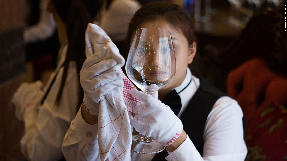 A student polishes glassware in preparation for a formal dinner on September 16, 2014.