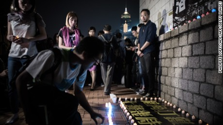 Tsang looks on as supporters lay candles at the spot where he was allegedly beaten by police in Hong Kong on late October 14, 2015.