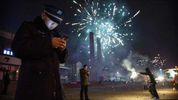 BEIJING, CHINA - February 19: A Chinese security guard checks his smartphone as fireworks explode during celebrations of the Lunar New early on February 19, 2015 in Beijing, China.The Chinese Lunar New Year of Sheep also known as the Spring Festival, which is based on the Lunisolar Chinese calendar, is celebrated from the first day of the first month of the lunar year and ends with Lantern Festival on the Fifteenth day. (Photo by Kevin Frayer/Getty Images)