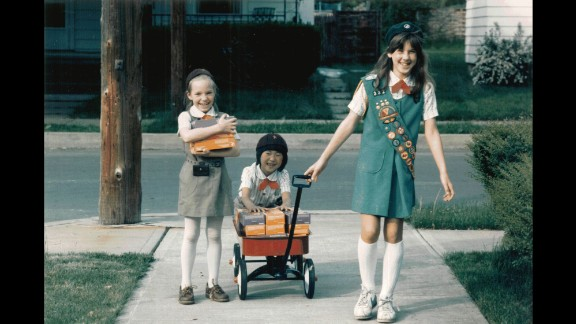 """1980s: A Girl Scout Junior helps Girl Scout Brownies with cookie deliveries, circa 1984. """"Cookies are so much more than a fundraiser,"""" says psychologist Andrea Bastiani Archibald, the Girl Scouts' chief girls expert. """"When someone buys a box of cookies, they're helping girls develop their financial literacy skills, their social skills ... and their business ethics. Girls  can carry these skills into the rest of their lives."""""""
