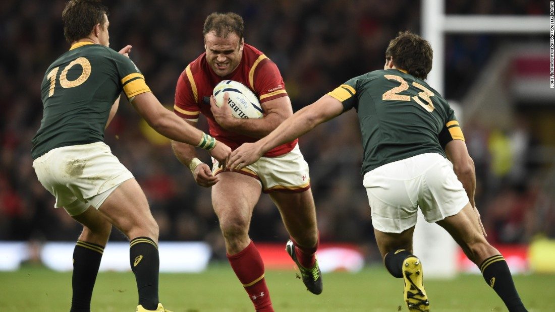 Wales' centre Jamie Roberts (C) runs with the ball  as South Africa's fly half Handre Pollard (L) and South Africa's centre Jan Serfontein (R) wait to tackle.