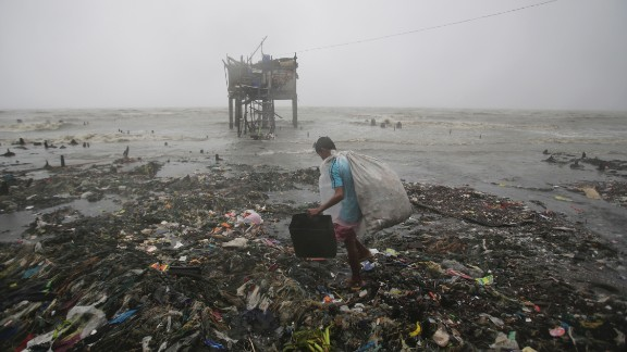 A man scavenges recyclable materials near a house on stilts as strong winds and rains hit the coastal town of Navotas on October 18.