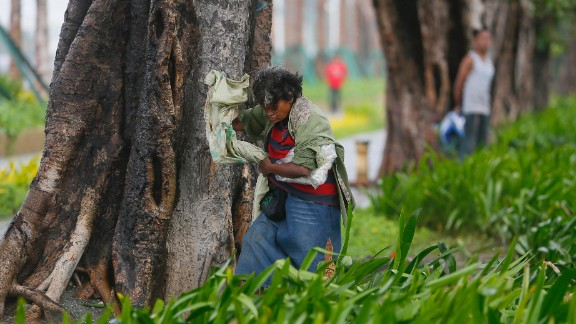 A woman seeks shelter from strong winds in Manila on October 18.