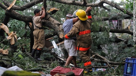 Fire volunteers and workers clear a fallen tree in Manila on October 19, 2015, after it toppled on October 18 and crushed a house, killing Ronel Castillo, a 14-year-old boy, and injuring four other people, Alexander Pama, head of the National Disaster Risk Reduction Council, told reporters. Residents trapped on rooftops by rising flood waters waited for rescue on October 19 as Typhoon Koppu flogged the Philippines for a second day, after killing two people and leaving thousands temporarily homeless.  AFP PHOTO / Jay DIRECTO        (Photo credit should read JAY DIRECTO/AFP/Getty Images)