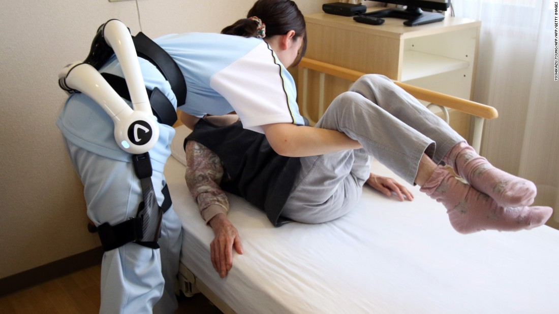 A care worker lifts a patient at the Fuyoen nursing home for elderly people. She's wearing Cyberdyne's Hybrid Assistive Limb (HAL) robot suit during a demonstration on June 12, 2015. The HAL learns its users motions and provides stability and strength.